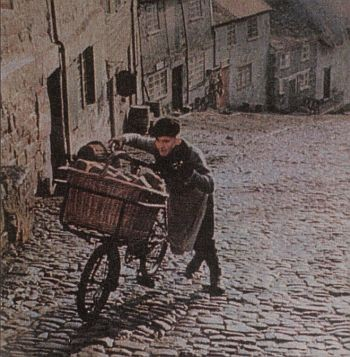 A young boy pushing a bike up a street